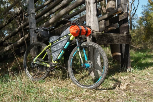 A bike with some gear packed on it next to a primitive wooden structure.  Bug out bicycles need to carry survival supplies as well as people.