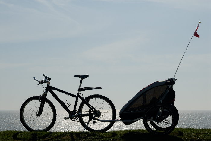 A bike with a trailer attached to it next to a water setting.  Adding a trailer to a bug out bicycle can greatly increase the amount of supplies you can bring with you in an emergecy.