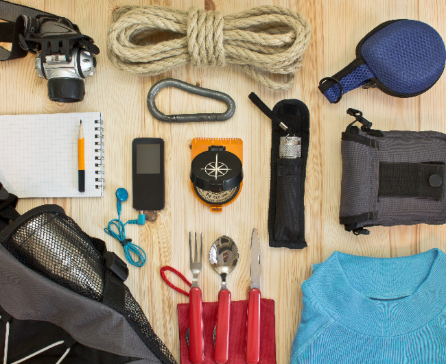 Overhead view of survival supplies on a wooden table.  Urban bug out bags need specialized supplies for city emergencies and disasters.