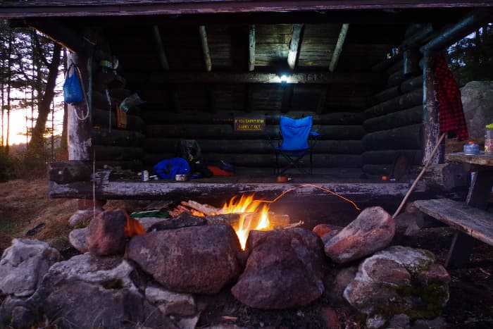 A rustic log shelter with a raised floor, rock fire pit , and overhanging roof -- a great example of a long term survival shelter.