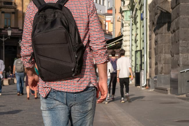 Man viewed from the back wearing a black backpack in an urban setting.  Even a basic backpack can become an urban bug out bag.