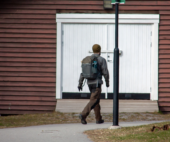 Man in cold weather clothing wearing a gray backpack walking down a sidewalk.  The ideal urban bug out bag is nondescript and doesn't attract attention.