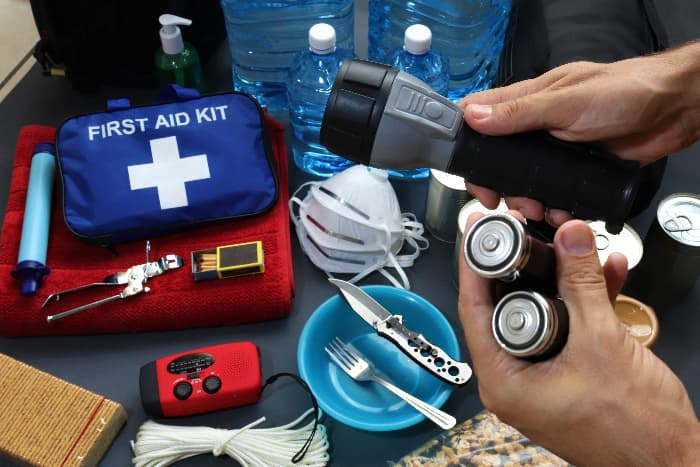 Closeup of first aid kit, flashlight, bottled water, and other basic survival supplies that should be included in every urban bug out bag