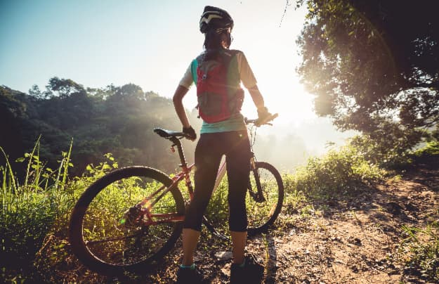 A woman cyclist standing next to her bike on a nature trail.